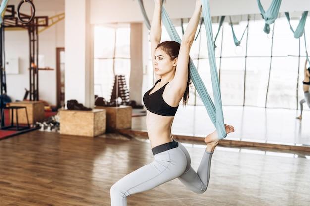 Giovane ragazza di forma fisica del corpo abbastanza esile che pratica yoga della mosca nella palestra.
