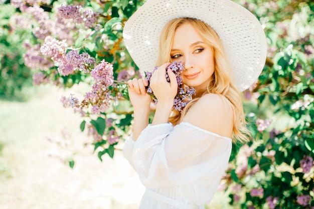 Giovane ragazza di modello stupefacente bionda graziosa sveglia in ritratto bianco del vestito in parco all'aperto.