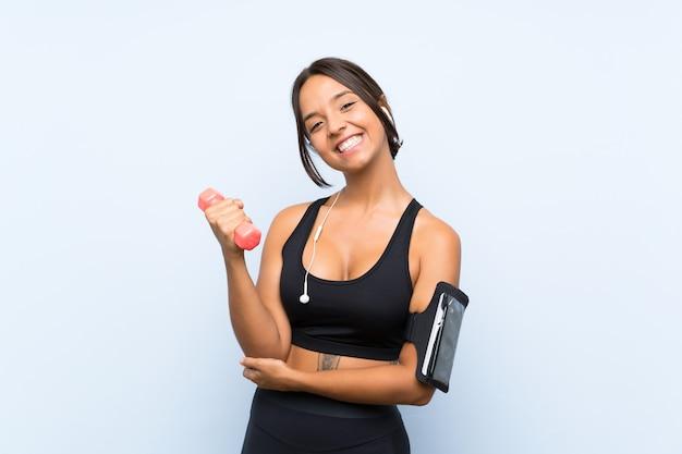 Giovane ragazza di sport che fa sollevamento pesi sopra la parete blu isolata
