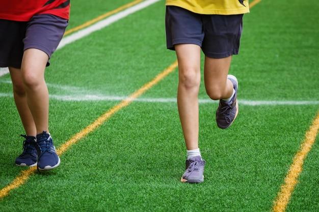 Giovane ragazza di sport che funziona sul campo di sport