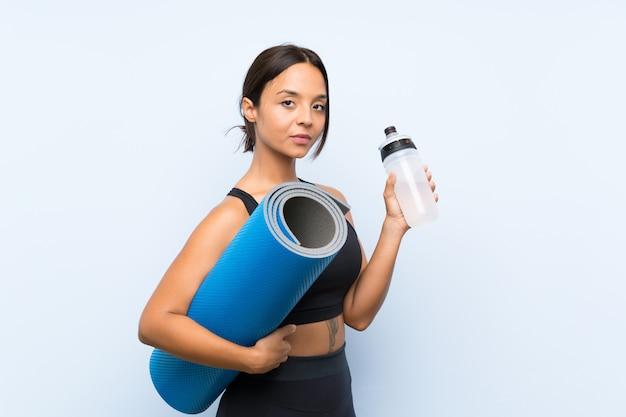 Giovane ragazza di sport con la stuoia e con una bottiglia di acqua sopra il blu isolato