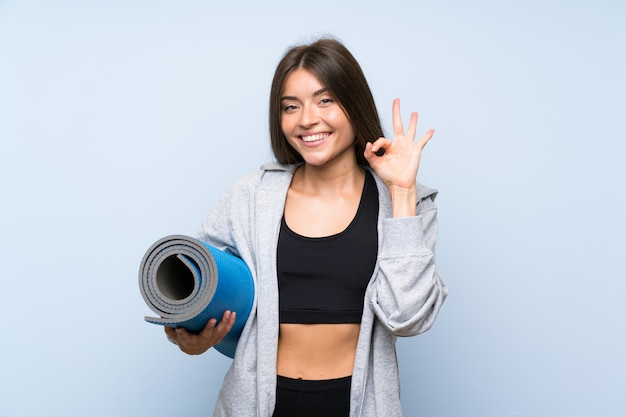 Giovane ragazza di sport con la stuoia sopra la parete blu isolata che mostra segno giusto con le dita