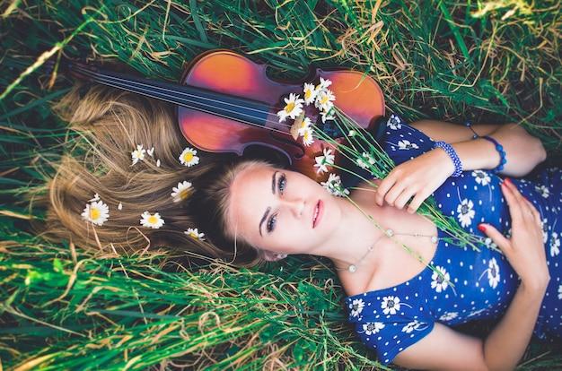 Giovane ragazza distesa in erba alta con margherite e violino