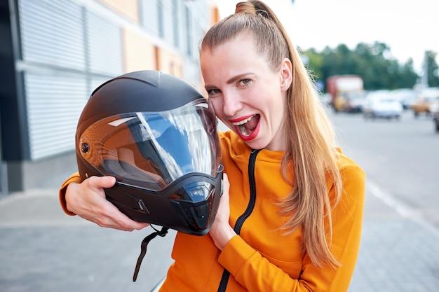 Giovane ragazza divertente attraente con le labbra dipinte rosse che posano con il casco nero.
