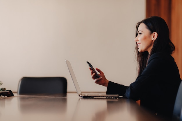 Giovane ragazza emotiva attraente in abiti stile business, seduto a una scrivania su un computer portatile e telefono in ufficio o sala