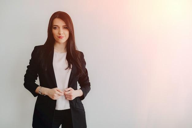 Giovane ragazza emotiva attraente in abiti stile business su un semplice sfondo bianco in un ufficio o pubblico
