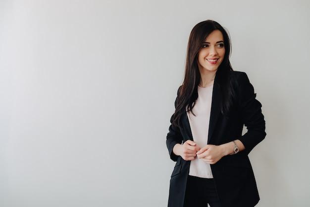 Giovane ragazza emotiva attraente in abiti stile business su una semplice superficie bianca in un ufficio o pubblico