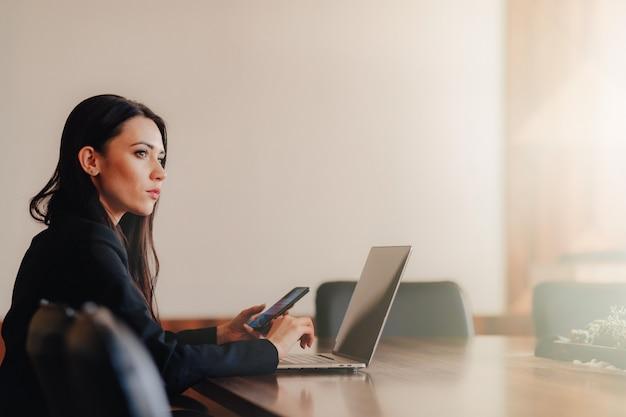 Giovane ragazza emotiva attraente in stile business vestiti seduto a una scrivania su un computer portatile e telefono