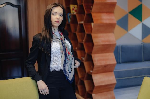 Giovane ragazza emotiva attraente in uno stile aziendale presso una sedia in un moderno ufficio o pubblico