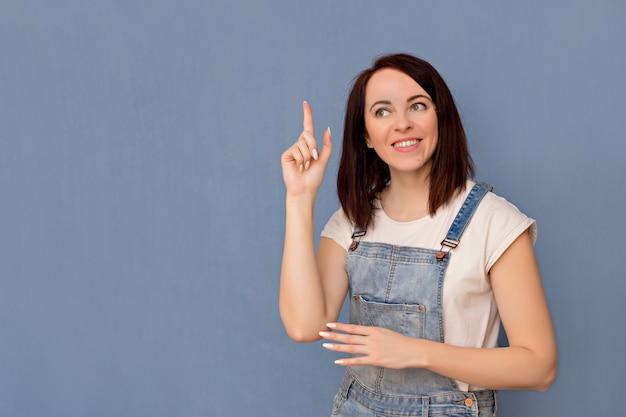 Giovane ragazza emotiva su una parete blu. gesti.