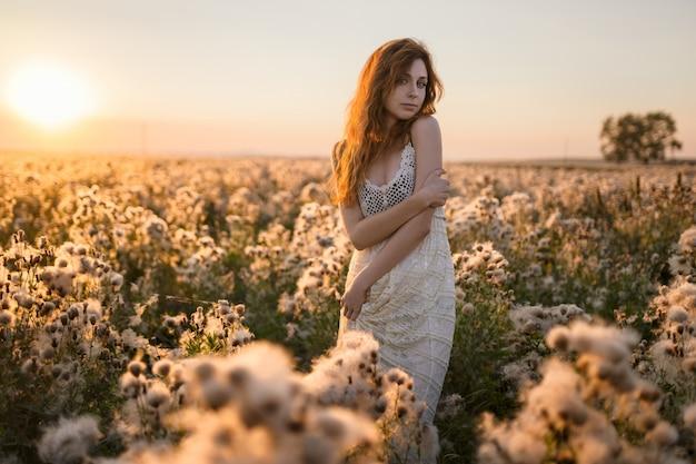 Giovane ragazza europea su un campo con una corona di erbe e un abito bianco