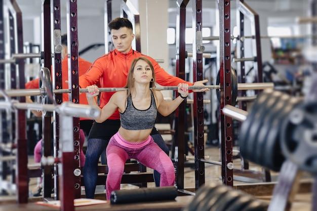 Giovane ragazza facendo squat con un bilanciere in palestra sotto la supervisione di un allenatore