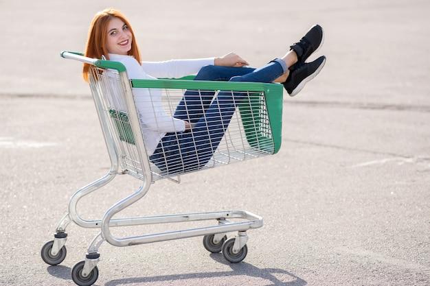 Giovane ragazza felice adolescente che si siede in carrello del supermercato all'aperto.