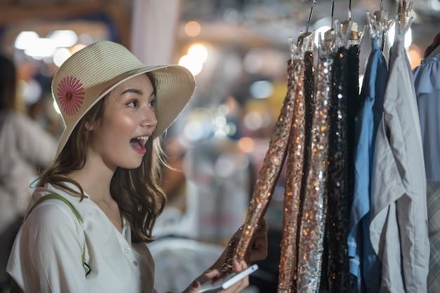 Giovane ragazza felice asiatica che cammina per la compera al mercato di notte.