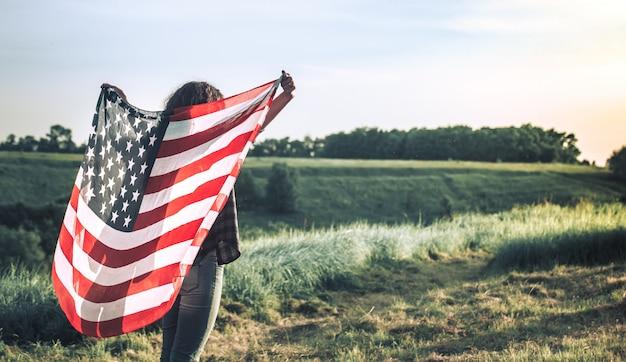 Giovane ragazza felice che corre e che salta spensierata con a braccia aperte sopra il campo di frumento. tenendo la bandiera degli stati uniti.