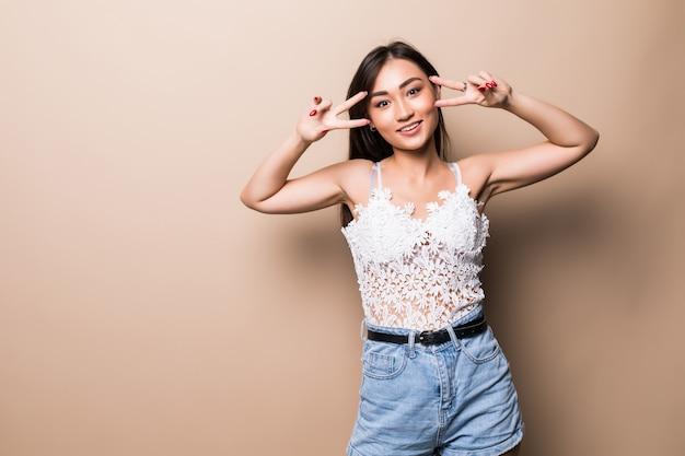 Giovane ragazza giapponese felice che mostra il segno di vittoria isolato sulla parete beige