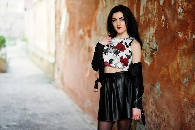 Giovane ragazza goth sulla gonna di pelle nera e giacca contro la parete del grunge.