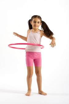 Giovane ragazza graziosa che gioca il cerchio di hula