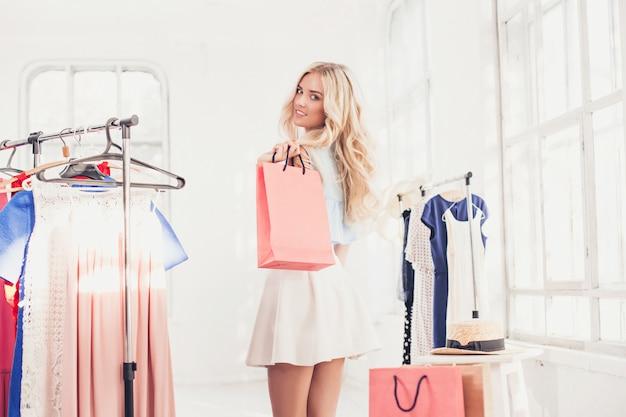 Giovane ragazza graziosa che sceglie e che prova sui vestiti al negozio