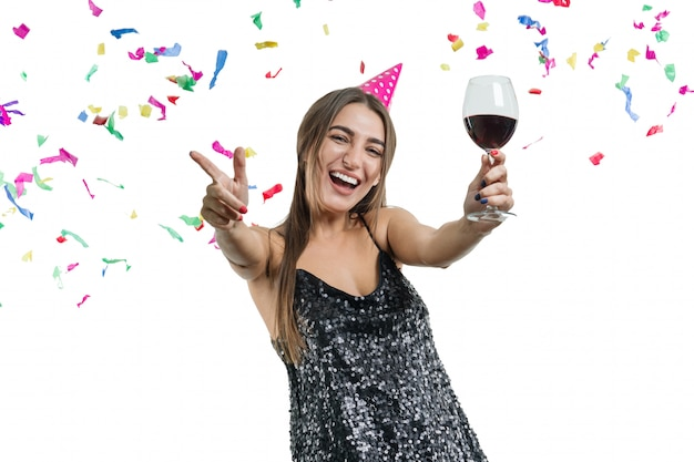 Giovane ragazza graziosa del brunette in cappello del partito con bicchiere di vino rosso