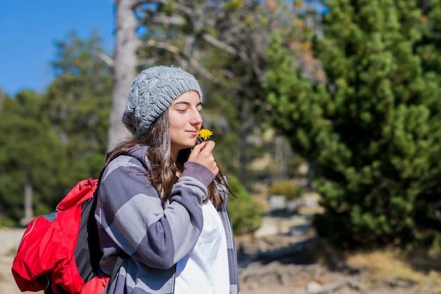 Giovane ragazza graziosa di viaggiatore con zaino e sacco a pelo in cappello di lana che sta nella foresta mentre odorando un fiore