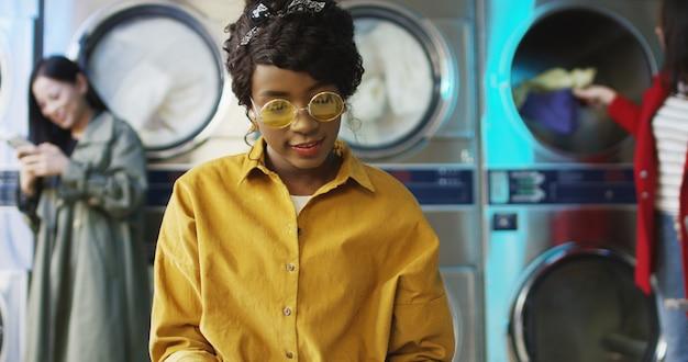 Giovane ragazza graziosa ed alla moda dell'afroamericano in vetri gialli che si levano in piedi nella stanza di servizio di lavanderia e lanciando le pagine del giornale di modo. rivista di lettura donna in attesa di lavare i vestiti.