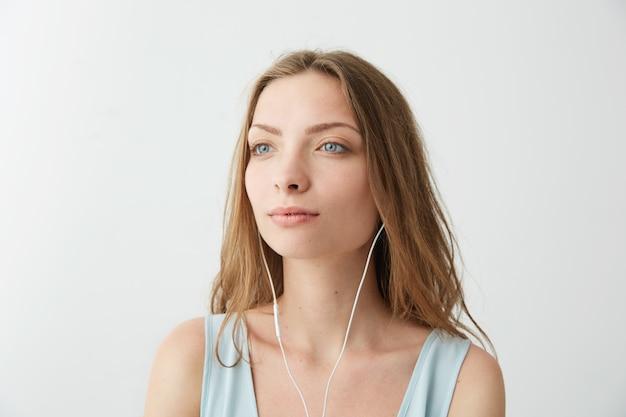 Giovane ragazza graziosa sognante tenera che sogna ascoltare la musica in streaming in cuffia.