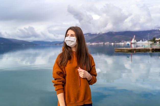 Giovane ragazza in strada della città che indossa una maschera protettiva per la diffusione della malattia di coronavirus 2019.