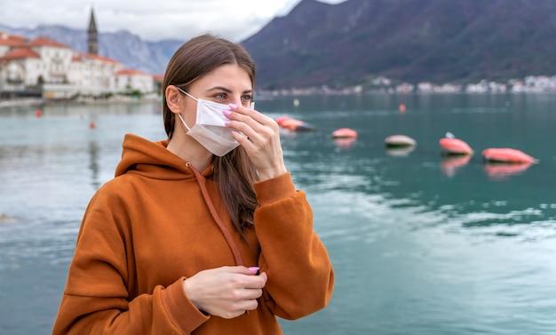 Giovane ragazza in strada della città che indossa una maschera protettiva per la diffusione della malattia di coronavirus