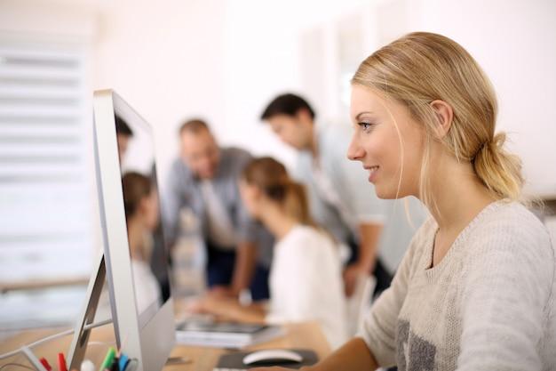 Giovane ragazza in ufficio a lavorare su computer desktop