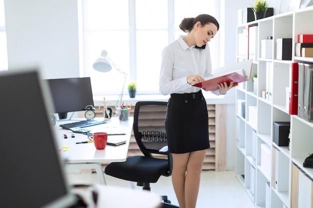 Giovane ragazza in ufficio vicino al rack e scorre attraverso la cartella con i documenti e parla al telefono