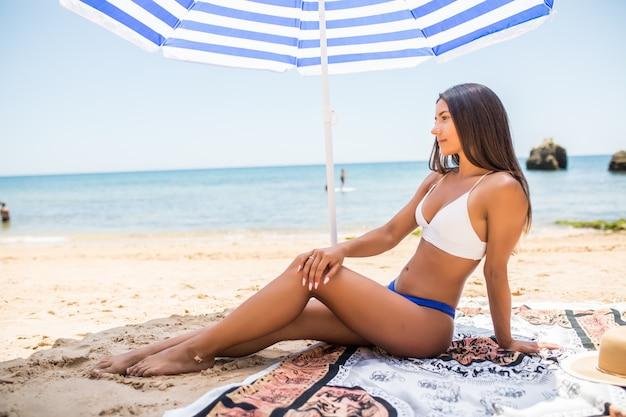Giovane ragazza latina in bikini che si trova sotto l'ombrello di colore sulla spiaggia nella soleggiata giornata calda.
