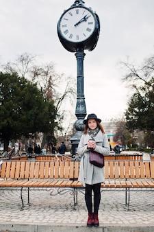 Giovane ragazza modello in un cappotto grigio e cappello nero con borsa in pelle sulle spalle rimanere con una tazza di caffè in plastica