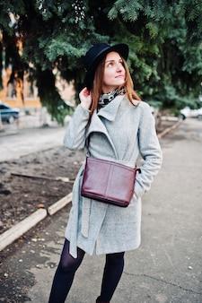 Giovane ragazza modello in un cappotto grigio e cappello nero con borsetta in pelle sulle spalle poste sulla strada della città.