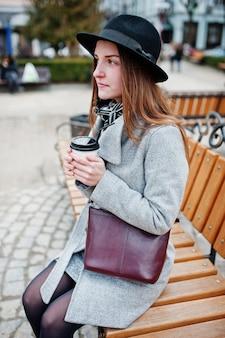 Giovane ragazza modello in un cappotto grigio e cappello nero con borsetta in pelle sulle spalle seduto sulla panchina con una tazza di caffè in plastica