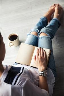 Giovane ragazza moderna in jeans strappati leggendo un libro con una grande tazza di caffè. moda, stile di vita, educazione ricreativa, hobby.