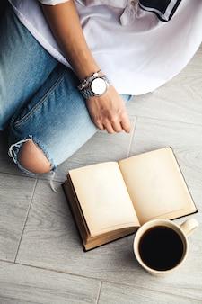 Giovane ragazza moderna in jeans strappati leggendo un libro con una grande tazza di caffè. moda, stile di vita, stile di vita, ricreazione, istruzione, hobby e