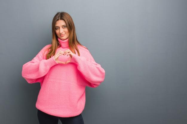 Giovane ragazza naturale russa che fa un cuore forma con le mani