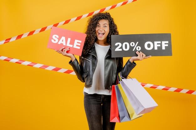 Giovane ragazza nera d'avanguardia con il segno del 20% di vendita e sacchetti della spesa variopinti isolati sopra giallo con nastro adesivo