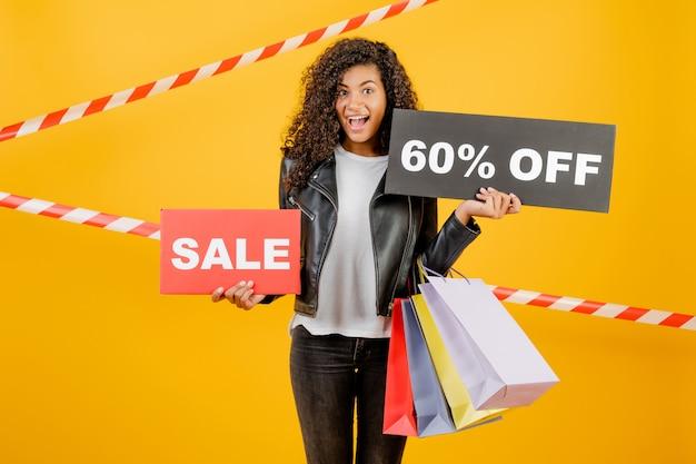 Giovane ragazza nera d'avanguardia con il segno del 60% di vendita e sacchetti della spesa variopinti isolati sopra giallo con nastro adesivo