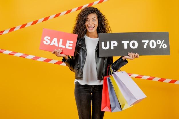 Giovane ragazza nera d'avanguardia con il segno del 70% di vendita e sacchetti della spesa variopinti isolati sopra giallo con nastro adesivo