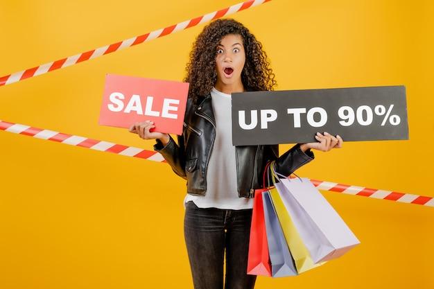 Giovane ragazza nera d'avanguardia con il segno del 90% di vendita e sacchetti della spesa variopinti isolati sopra giallo con nastro adesivo