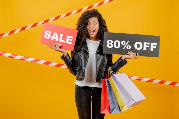 Giovane ragazza nera d'avanguardia con il segno dell'80% di vendita e sacchetti della spesa variopinti isolati sopra giallo con nastro adesivo