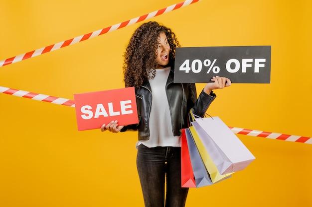 Giovane ragazza nera d'avanguardia con il segno di vendita del 40% e sacchetti della spesa variopinti isolati sopra giallo con nastro adesivo