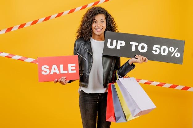 Giovane ragazza nera d'avanguardia con il segno di vendita del 50% e sacchetti della spesa variopinti isolati sopra giallo con nastro adesivo