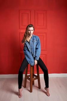 Giovane ragazza o modello attraente con capelli lunghi, vestito con una giacca di jeans e pantaloni neri, ubicazione sulla sedia.