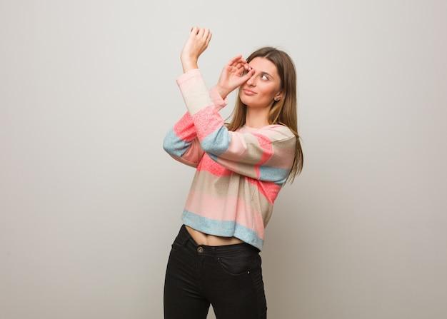 Giovane ragazza russa che rende al gesto un cannocchiale
