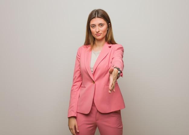 Giovane ragazza russa di affari che raggiunge fuori per accogliere qualcuno