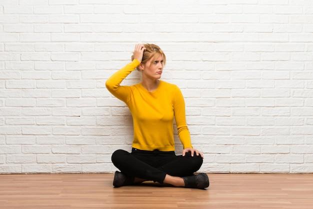 Giovane ragazza seduta sul pavimento con dubbi mentre grattando la testa