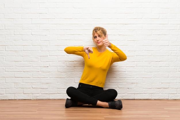Giovane ragazza seduta sul pavimento facendo buon-segno. indeciso tra sì o no